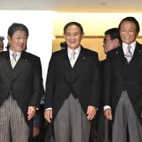 Prime Minister Yoshihide Suga smiles along with Foreign Minister Toshimitsu Motegi (left) and Finance Minister Taro Aso (right) Wednesday night after forming his Cabinet. | KYODO