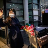 Filipino nurse April Glory waves to her family before leaving for the U.K. in August after the government partially eased restrictions on health workers' movements.  | REUTERS