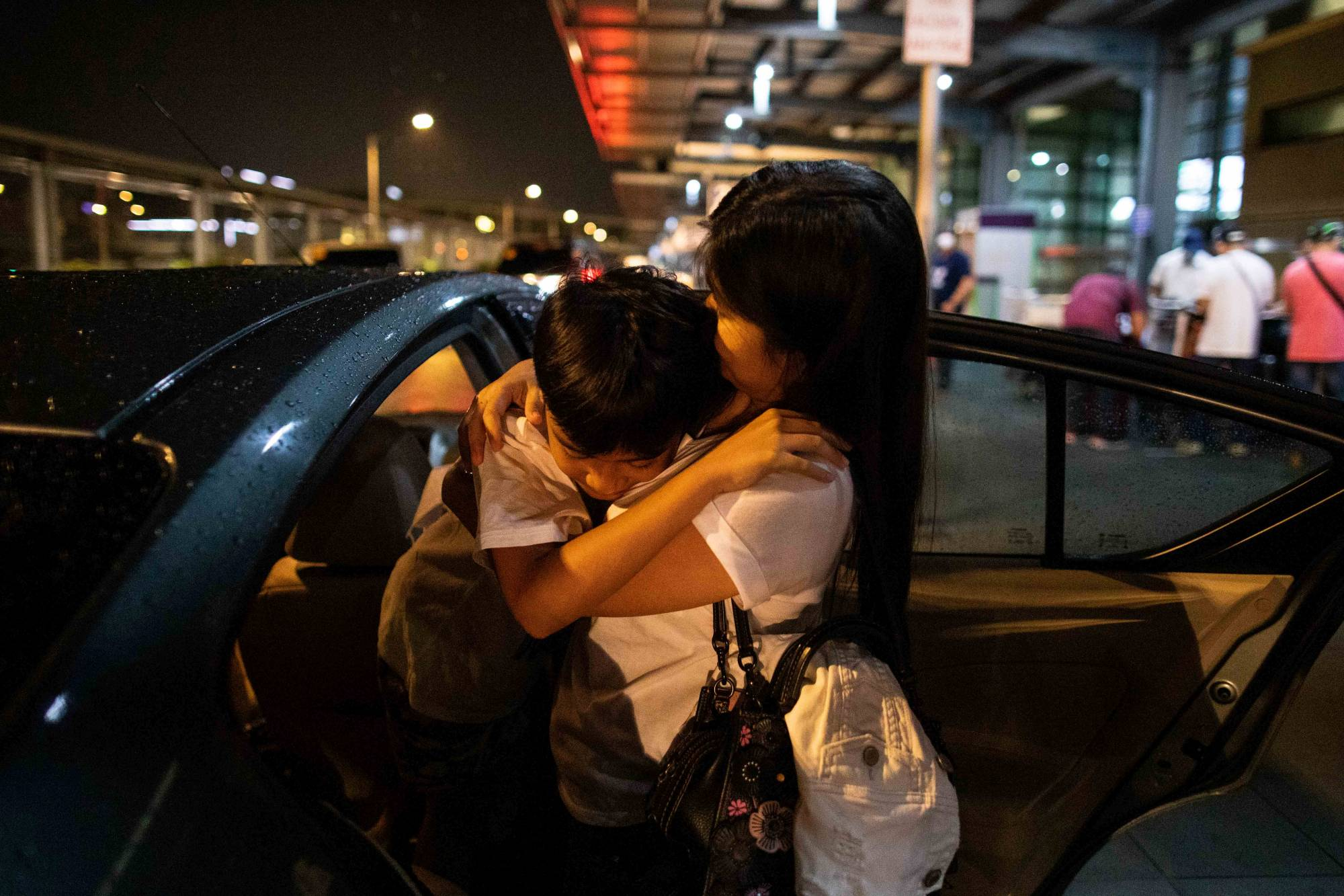 April Glory hugs her son before leaving for the U.K. | REUTERS