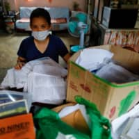 Dean, who asked that her surname not be used, is photographed at her family's home in Metro Manila with boxes of documents she used to apply for a nursing job in the U.K.  | REUTERS