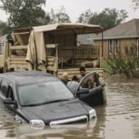 Members of the Florida National Guard rescue residents from their flooded vehicle in Cantonment, Florida, on Wednesday, after Hurricane Sally slowly moved through the area. | WILLIAM WIDMER / THE NEW YORK TIMES