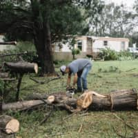 Tim Booth, 62, begins to cut and clear downed trees from the front yard of his home in Loxley, Alabama, on Wednesday. | WILLIAM WIDMER / THE NEW YORK TIMES