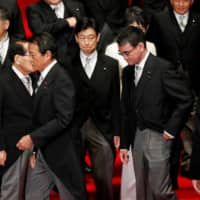 Deputy Prime Minister and Finance Minister Taro Aso (left) alongside Taro Kono, administrative reform minister (front right), leave a photo session with Prime Minister Yoshihide Suga (not pictured) and other Cabinet ministers on Wednesday. | REUTERS