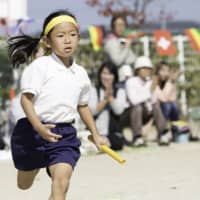 Try your best: A young girl takes part in a traditional school 'taiikusai' (sports festival), which are often held in the fall.   GETTY IMAGES
