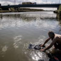 Falah, an Iraqi migrant and a father of two girls, washes clothes in a river at a makeshift migrants camp in Dunkirk, northern France, earlier this month.  | AFP-JIJI