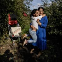 Arwa (left), 10, and her sister Rawane, 13, embrace at a makeshift migrants camp in Dunkirk, northern France, earlier this month. | AFP-JIJI