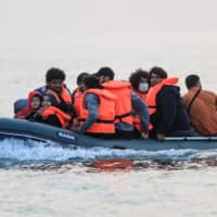 Waleed (right), a Kuwaiti migrant, and others sit in a dinghy as they illegally cross the English Channel from France to Britain on Sept. 11.  | AFP-JIJI