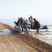A group of people thought to be migrants arrive via an inflatable boat at Kingsdown beach after crossing the English Channel, near Dover, England, earlier this month.  | PA / VIA AP