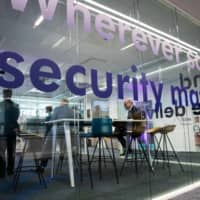 A security sign is printed on a glass surface in an office space during the Thales SA cybersecurity event in Paris in April 2018. | BLOOMBERG