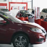 Nissan brand passenger cars are displayed at a Dongfeng Motor Co. dealership in Beijing in April. | KYODO