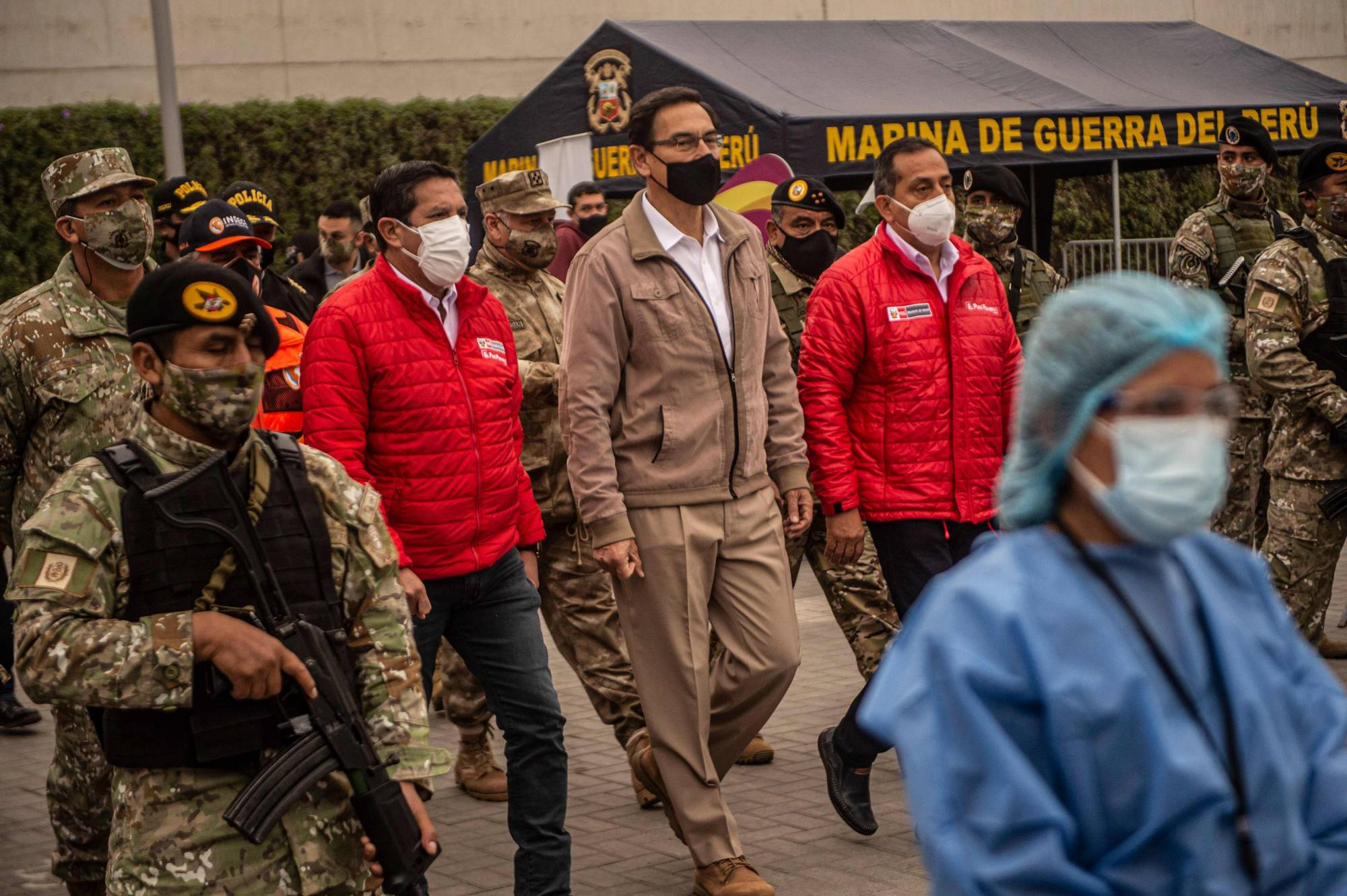 Peru's president, Martin Vizcarra (center), who's national economy is one of the worst performing globally amid the COVID-19 pandemic, oversees the distribution of supplies to those in need on the outskirts of Lima on Tuesday. | AFP-JIJI