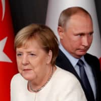 German Chancellor Angela Merkel and Russian President Vladimir Putin arrive for a news conference in Istanbul in October 27 2018.  | REUTERS