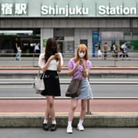 Women use their smartphones outside JR Shinjuku Station in downtown Tokyo on Monday. | AFP-JIJI