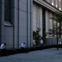 Workers take a lunch break in Tokyo's Marunouchi district earlier this month amid the coronavirus pandemic. | BLOOMBERG