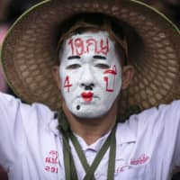 A pro-democracy protester with a painted face reading 'Sept. 19 Coup' protests at the Thammasat University in Bangkok on Saturday. | AP