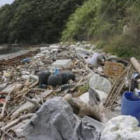 Piles of plastic waste are washed ashore on a beach in Uwajima, Ehime Prefecture. | KYODO