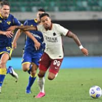 Roma forward Justin Kluivert (right) and Verona defender Salvatore Bocchetti fight for the ball during an Italian first-division match on Saturday in Verona, Italy. | AFP-JIJI