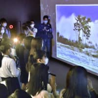 Visitors watch a video showing scenes from the March 2011 triple disaster at The Great East Japan Earthquake and Nuclear Disaster Memorial Museum in Futaba, Fukushima Prefecture, on Sunday. | KYODO