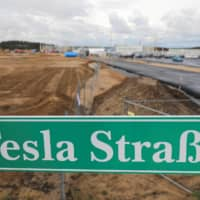 A sign that reads 'Tesla Street' is pictured outside the construction site of the future Tesla Gigafactory in Gruenheide, near Berlin, on Sept. 2. | REUTERS