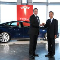 Tesla's Elon Musk hands a key to Panasonic's Yoshihiko Yamada during a ceremony in Tokyo in 2014.  | BLOOMBERG
