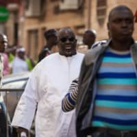 Papa Massata Diack (center) arrives at a police station in Dakar, the capital of Senegal, in February 2016. | AP / VIA KYODO