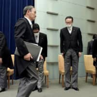 Chief Cabinet Secretary Katsunobu Kato (left) bows as Prime Minister Yoshihide Suga (front) leaves a conference room at his office in Tokyo after a news conference Wednesday.   | KYODO
