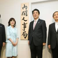 (From left) Katsunobu Kato, then-head of the Cabinet Bureau of Personnel Affairs, Tomomi Inada, then-state minister in charge of civil servant system reform, Shinzo Abe, then-prime minister and Yoshihide Suga, then-chief Cabinet secretary, pose for a photo in Tokyo in May 2014 when the bureau was launched. | KYODO
