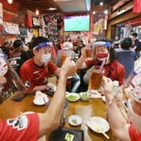 Red cards: Fans of J-League soccer club Urawa Reds wear face shields and masks while at a pub in Saitama to watch a match on TV.  | KYODO