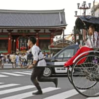 A man pulls a rickshaw in Tokyo's Asakusa tourist area on Monday, the third day of Japan's four-day holiday period.   KYODO