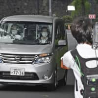 A police vehicle carrying Tatsuya Yamaguchi, a former member of all-male pop idol group Tokio, arrives at the Metropolitan Police Department's headquarters in Tokyo on Tuesday afternoon. | KYODO
