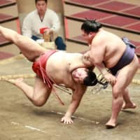 Onosho (right) slaps down Takayasu to remain tied for the lead during Day 10 of the Autumn Grand Sumo Tournament at Ryogoku Kokugikan on Tuesday. | NIKKAN SPORTS