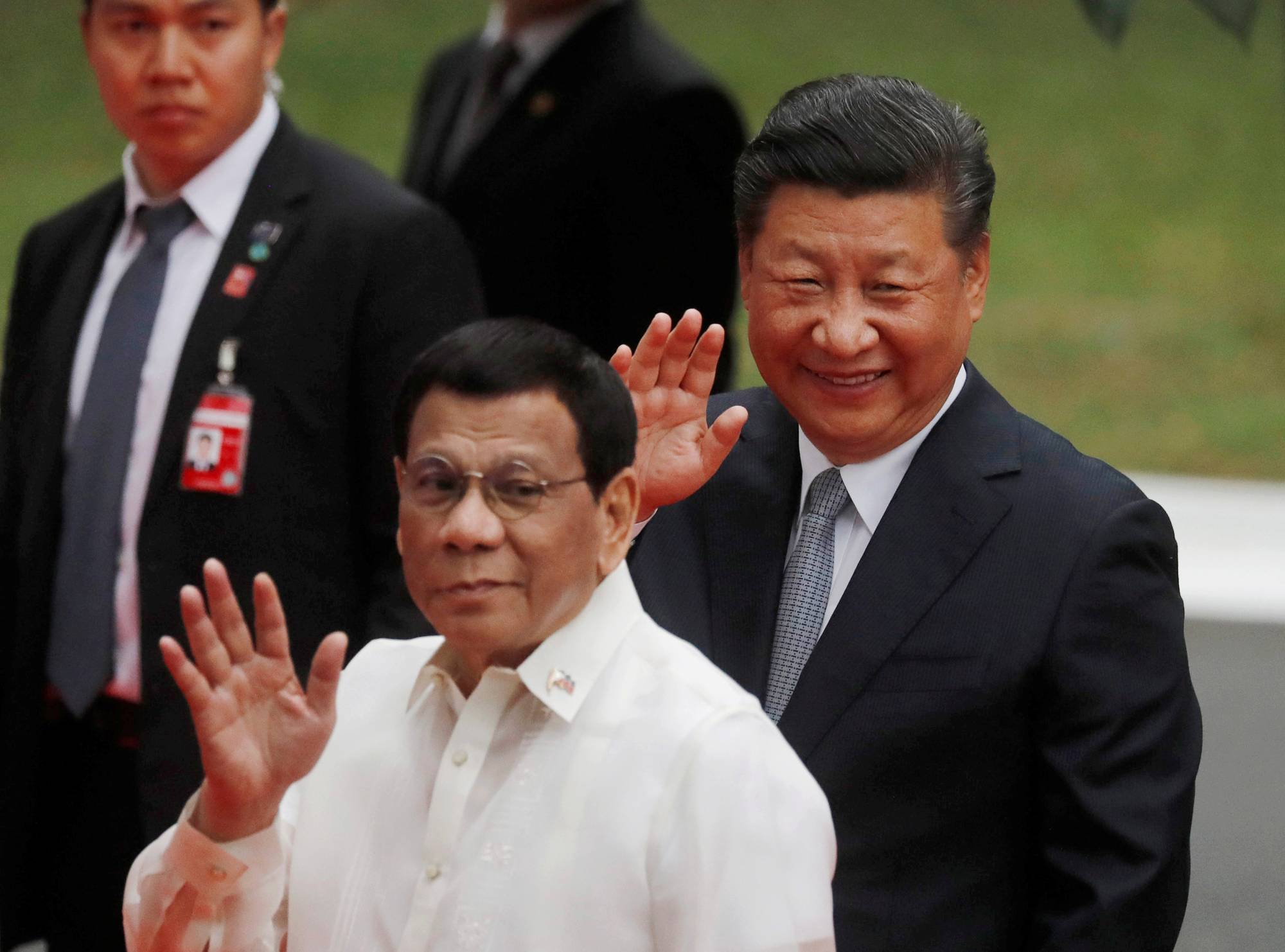 Visiting Chinese President Xi Jinping and Philippine President Rodrigo Duterte wave to the media before a meeting in Manila in 2018. | REUTERS