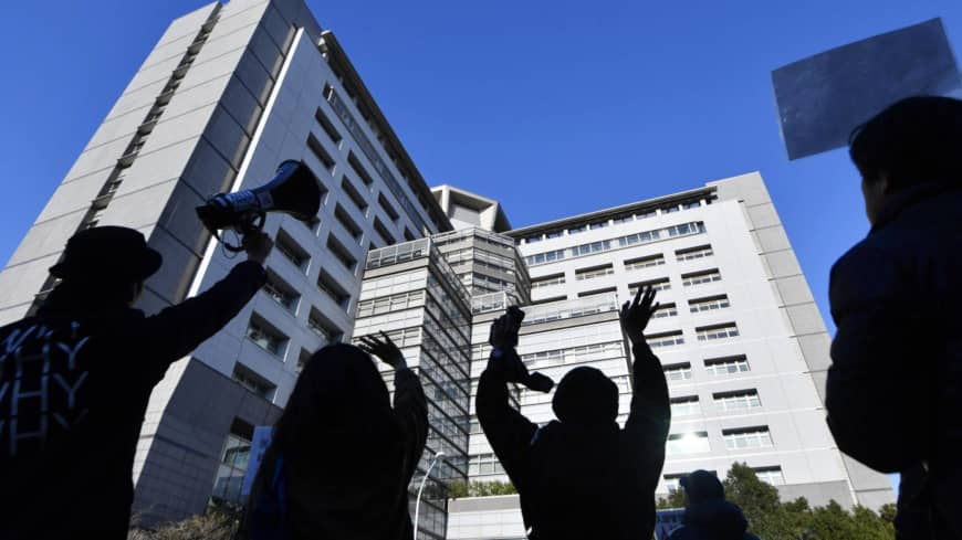 Protesters wave to people detained at the Tokyo Regional Immigration Bureau building in December, during a rally against long-term detainment of foreign nationals in Japan.