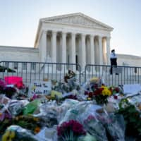 A makeshift memorial for Supreme Court Justice Ruth Bader Ginsburg outside the U.S. Supreme Court in Washington. Democrats and others worry that if Ginsburg is replaced by a hard-line conservative, Chief Justice John Roberts will no longer be the swing vote. | BLOOMBERG