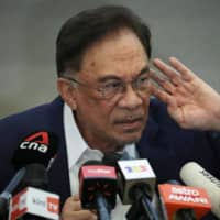 Malaysia opposition leader Anwar Ibrahim reacts during a news conference in Kuala Lumpur on Wednesday.  | REUTERS
