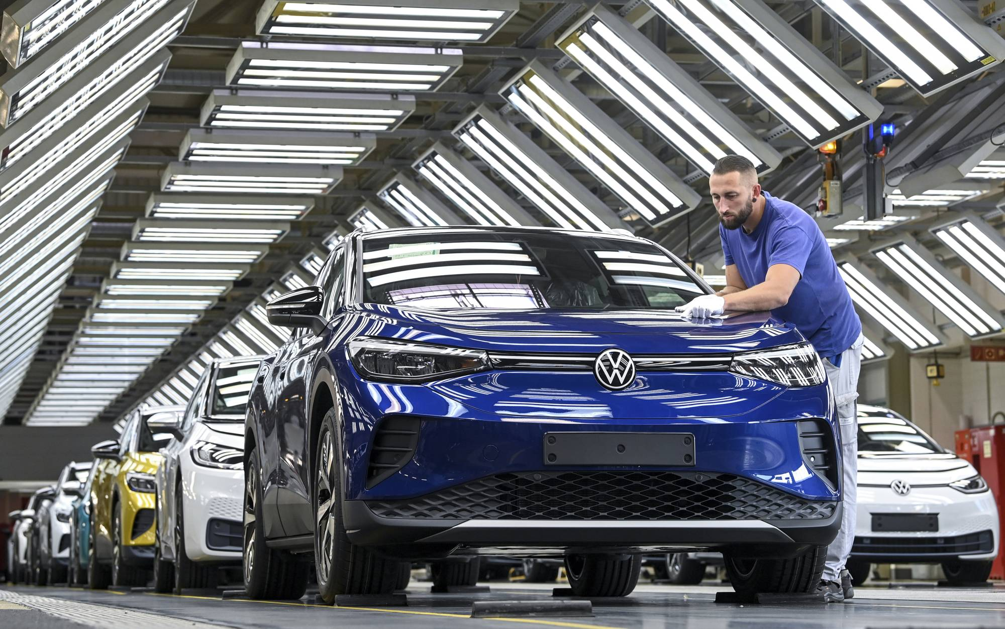 A worker puts the finishing touches on a battery-powered VW ID.4 at a plant in Zwickau, Germany, on Friday.  | DPA / VIA AP
