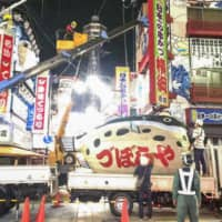 An iconic puffer fish-shaped paper lantern is taken down at Osaka's Shinsekai district on Sept. 3. The puffer fish restaurant Zuboraya decided to close after a century in business. | KYODO