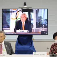 Thomas Bach, seen on screen during an IOC meeting on Thursday, said the 2020 Tokyo Olympics will be a historic event. | POOL / VIA AFP-JIJI