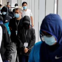 Mrs. Wong (center), the wife of Wong Wai Yin, one of 12 Hong Kong activists apprehended as they reportedly sailed to Taiwan for political asylum, arrives to attend a news conference in Hong Kong on Sept. 12.  | REUTERS