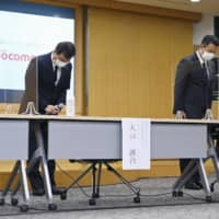 NTT Docomo Inc. Senior Executive Vice President Seiji Maruyama (left) apologizes to people whose bank deposits were stolen using its e-money service, at a news conference at its headquarters in Tokyo on Sept. 10. | KYODO