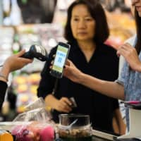 A customer holds up their smartphone for a QR code to be scanned at a grocery store in Bangkok in September 2017. | BLOOMBERG