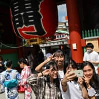 People pose at the entrance to Sensoji temple in Tokyo's Asakusa district on Tuesday. | AFP-JIJI