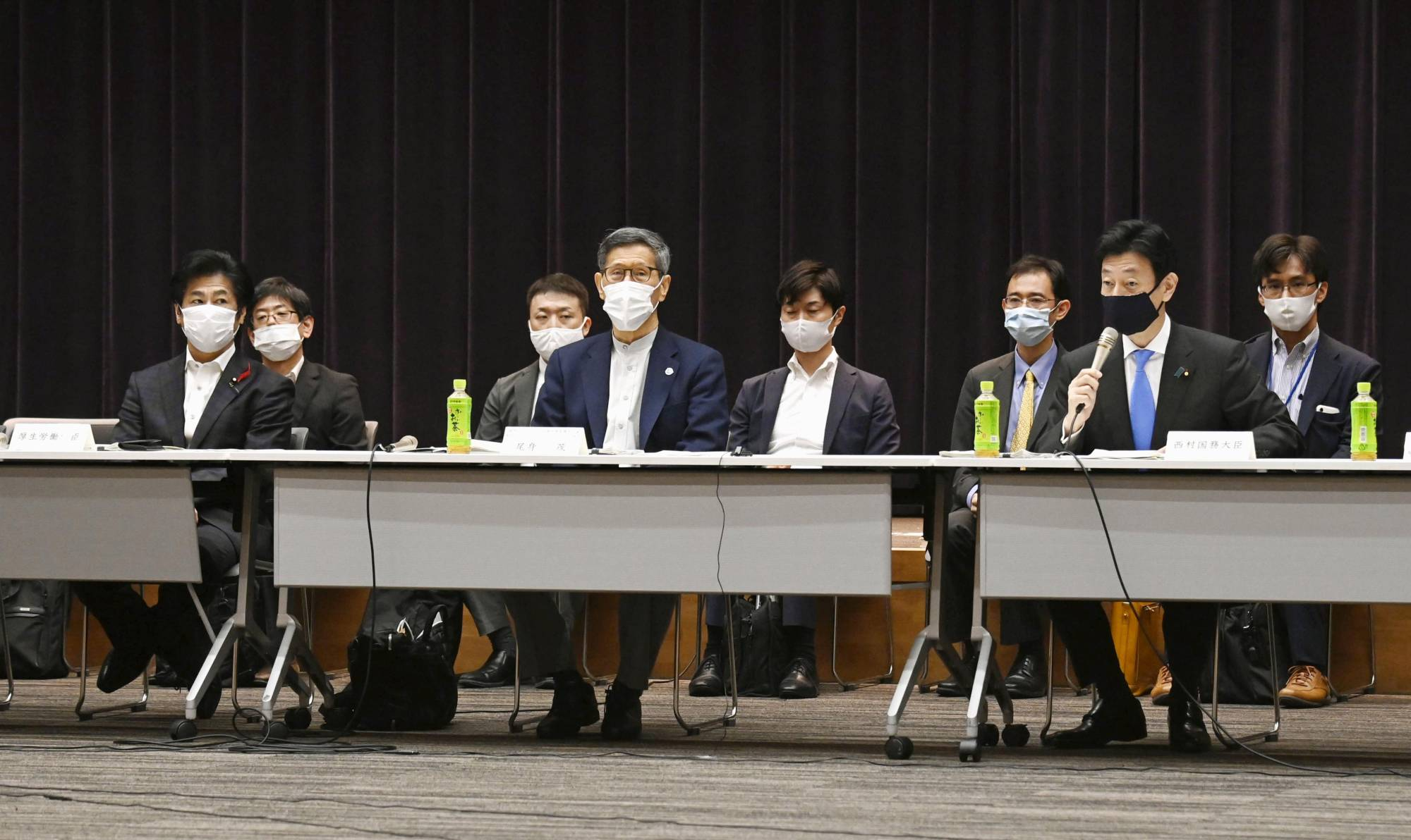 Shigeru Omi, who heads a government subcommittee on COVID-19 measures, and economic revitalization minister Yasutoshi Nishimura attend a meeting of the government's virus task force on Friday. | KYODO