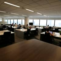 People work in an office where the majority of staff work remotely amid the coronavirus pandemic at the headquarters of Fujitsu in Tokyo last month. The central government plans to begin offering grants to municipalities that promote teleworking as a regional revitalization measure from fiscal 2021. | REUTERS