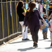 Children are greeted on their first day of preschool in New York on Monday. In adults, the immune response to the coronavirus is much more muted than in children, research has shown. | REUTERS