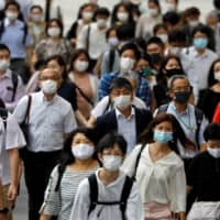 Commuters and passers-by wearing protective face masks walk near Tokyo Station amid the coronavirus pandemic in late July. | REUTERS