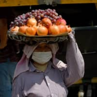 A vendor carries fruit for sale in Phnom Penh. In Cambodia, which reports being largely spared by the virus so far, there is a measure of schadenfreude toward the United States. | AFP-JIJI