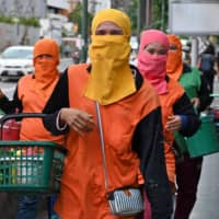Workers walk along a sidewalk in Bangkok. In March, the United States provided 10,000 gloves and 5,000 surgical masks, among other medical supplies, to Thailand, which today has recorded fewer than 3,520 coronavirus cases and 59 deaths. Despite the low caseload, most Thais continue to wear face masks in public, and the country never suffered a mask shortage. | AFP-JIJI