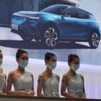 Receptionists with Chinese automaker Enovate wait for attendees of the Auto China 2020 show in Beijing on Saturday. | AP
