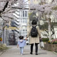 A mother and a child walk to a nursery in Osaka in April before the mother goes to work. | KYODO